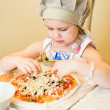 Little girl adding cheese in pizza — Stock Photo #10597355