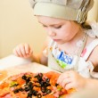 Little girl adding ingredients in pizza — Stock Photo #10597361