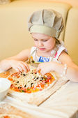 Little girl adding cheese in pizza — Stock Photo
