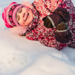 Stock Photo: Baby lays on snow and laugh