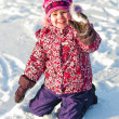 Stock Photo: Baby sits on snow and smile