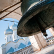Giant bell with church on background — Stock Photo