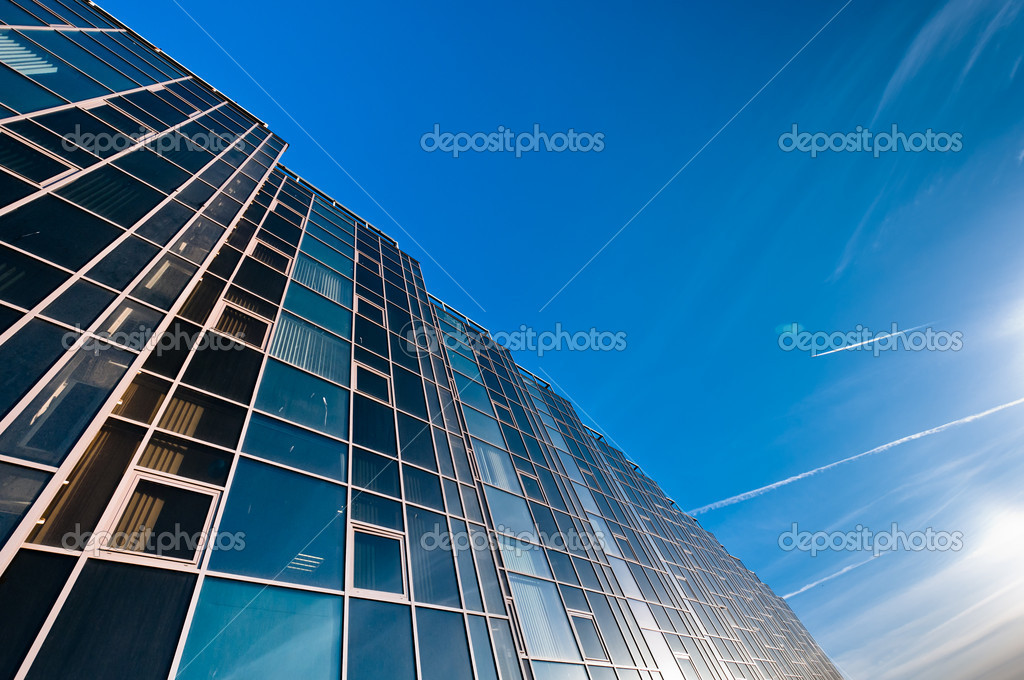 Glass wall of office building with deep blue sky on background  Stock Photo #9762072