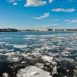 Broken ice pieces floating on river — Stockfoto