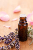 Lavendel and parfum bottle with rose leafs on wooden background — Stock Photo