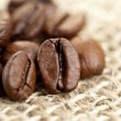 Brown Coffee Beans on a jute bag - Stock Photo