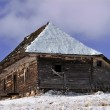 Abandoned wooden cottage in wintry view — Stock Photo