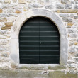 Wooden door on stone wall — Stock Photo