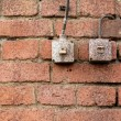Light switches on old weathered brick wall — Foto Stock