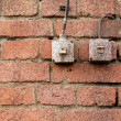 Light switches on old weathered brick wall — Stok fotoğraf