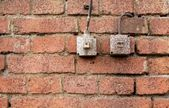 Light switches on old weathered brick wall — Stock Photo