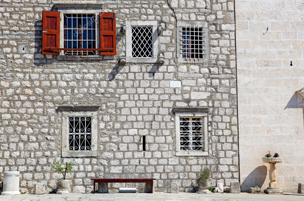 Double exterior with windows, bench, stones and flowers in pots — Stock Photo #10587072