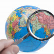 Terrestrial globe with magnifying glass — Stock Photo