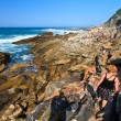 Women hiking along the Rocky coastline — Stock Photo