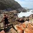 Woman hiking along the Rocky coastline — Stock Photo