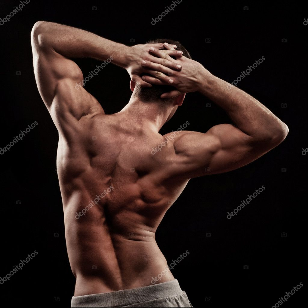 Strong athletic mans back on dark background — Stock Photo #9450906