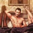 Foto Stock: Young man with two women in bedroom