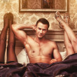 Young man with two women in bedroom - Stock Photo