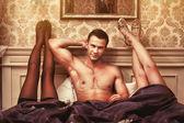 Jeune homme avec deux femmes dans la chambre à coucher — Photo