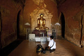 Praying in front of the statue of golden buddha in Htilominlo Pahto temple — Stock Photo