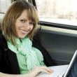 Young woman using laptop in the car — Stock Photo