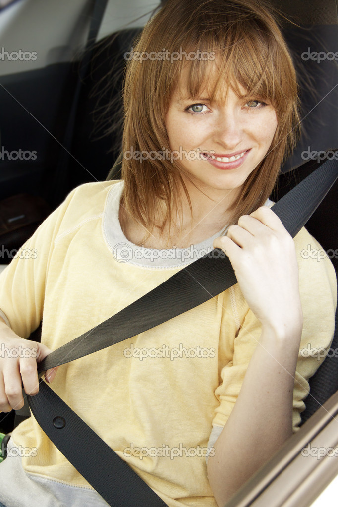 Smilling girl in the car putting on safety belt  Stock Photo #10541624