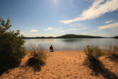 Alone on the Beach of a Calm Wilderness Lake — Stock Photo