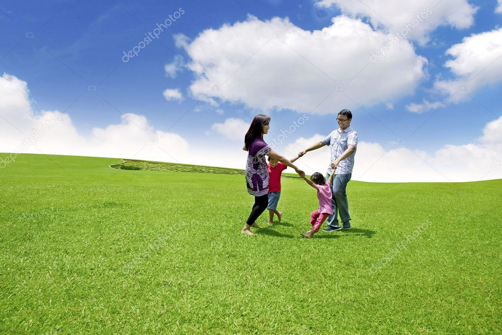 Happy asian family playing on the field. They are running in circle shot over blue sky — Stock fotografie #10040393