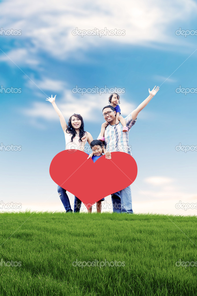 Happy Asian family carrying a heart cutout with copy space in meadow.  Stock Photo #10418147