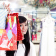 Smiling woman hiding behind her shopping bags — ストック写真