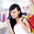 Asian woman with shopping bag and a credit card — Stock Photo