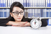 Businesswoman looking at alarm clock — Stock Photo