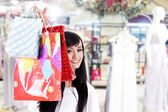 Uśmiechający się chowając się za jej torby na zakupy — Zdjęcie stockowe