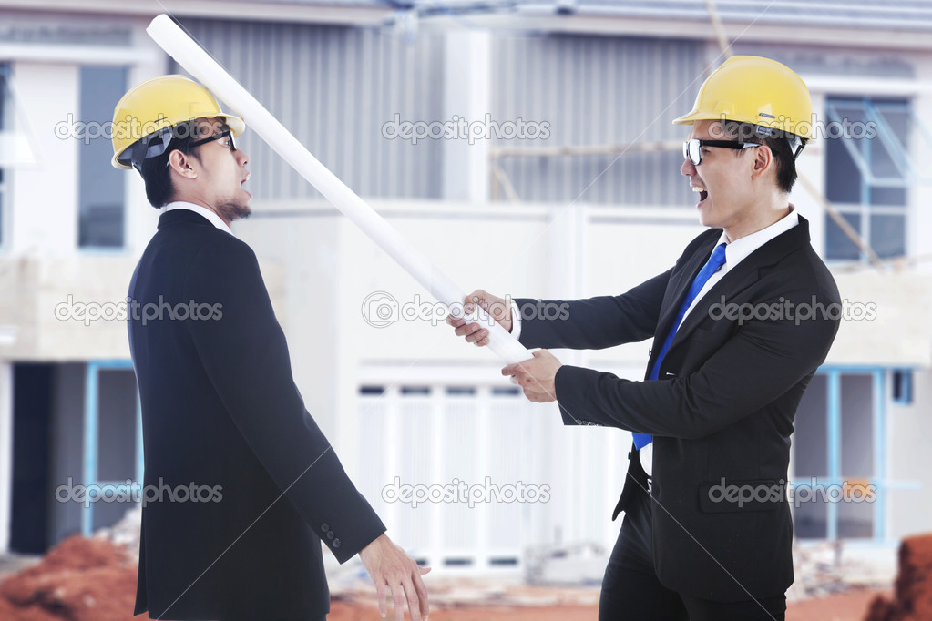 Business disagreement: an engineer hit his rival using blueprints shot at workplace outdoor — Stock Photo #10502241
