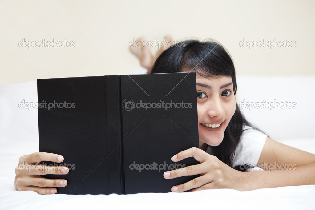 Beautiful Asian woman smiling while reading a book in a bedroom — Stock Photo #10502962