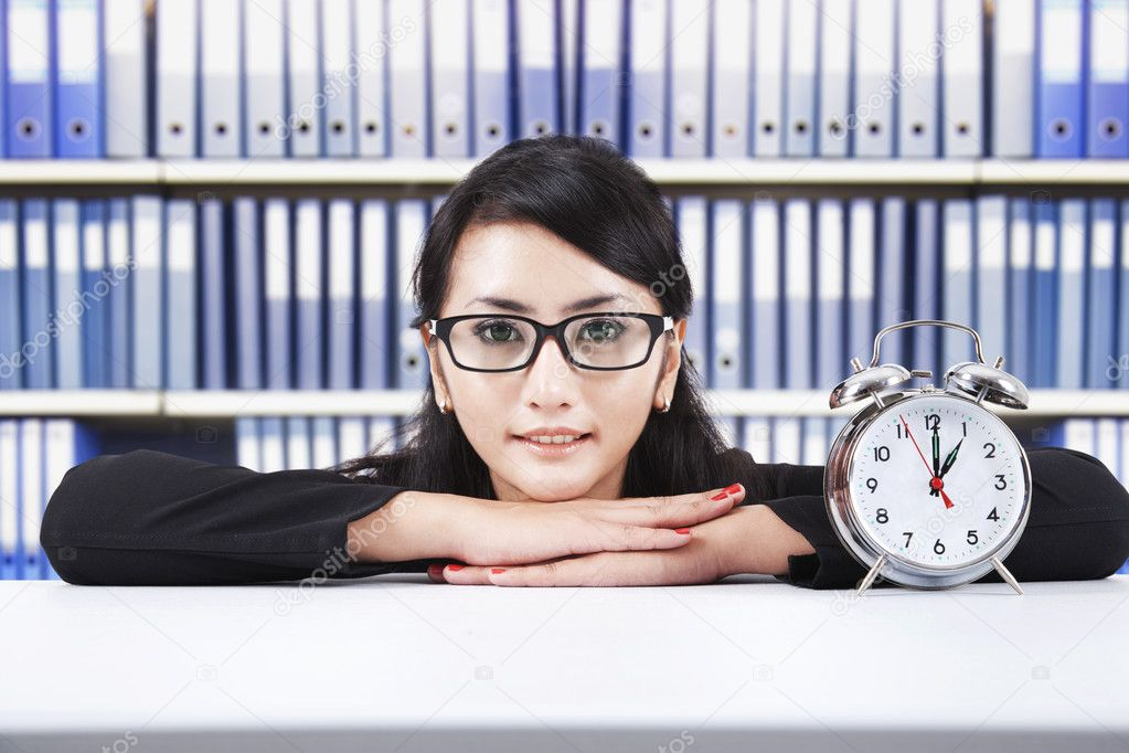 Smiling beautiful businesswoman with alarm clock, shot in the office — Stock Photo #10503241