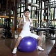 Asian woman posing with swiss ball in a gym — Stock Photo