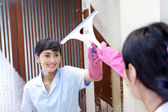 Asian woman cleaning up bathroom mirror — Stock Photo