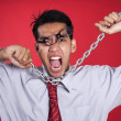 Freustrated businessman with chain shot over red — Stock Photo