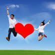 Flying couple with heart on blue sky — Stock Photo