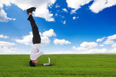 Businessman headstand outdoors — Stock Photo