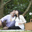 Pregnant couple blowing bubbles - Stock Photo