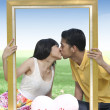 Young couple kissing with a frame — Stockfoto