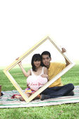Young couple with rectangle frame — Stock Photo