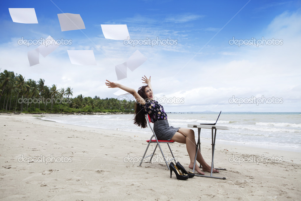 Happy asian businesswoman with working papers on the beach — Stock Photo #8606154