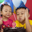 Kids blowing birthday candle — Stock Photo