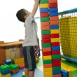 Boy seriously build tower block — Stock Photo