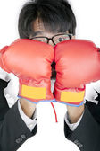 Scared Businessman protecting his face with boxing gloves — Stock Photo