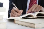 Closeup of businessman writing on a book — Foto de Stock