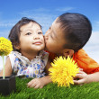 Boy kissing his sister in spring — Stockfoto